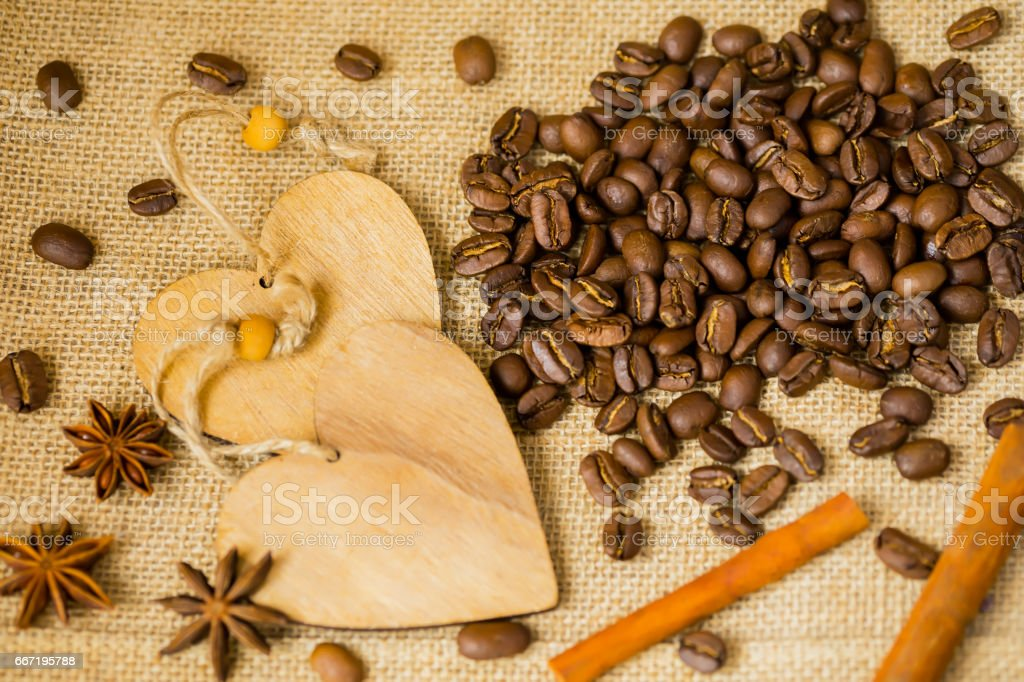 Grains of roasted coffee on sackcloth background with decorative wooden hearts. For creative concepts for any day or advertising with copy space. Coffee break concept stock photo