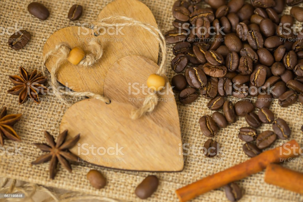 Grains of roasted coffee on sackcloth background with decorative wooden hearts. Coffee background with copy space for creative concepts for any day or advertising stock photo