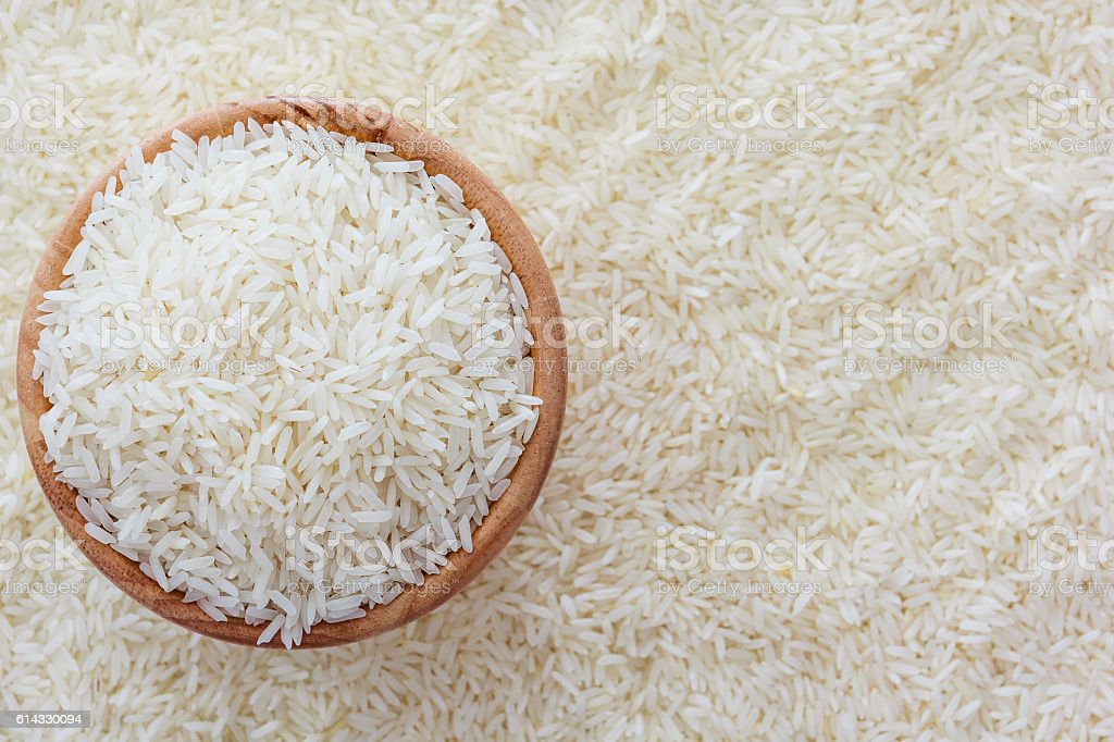 grains of Thai jasmine rice in wooden bowl on rice background stock photo