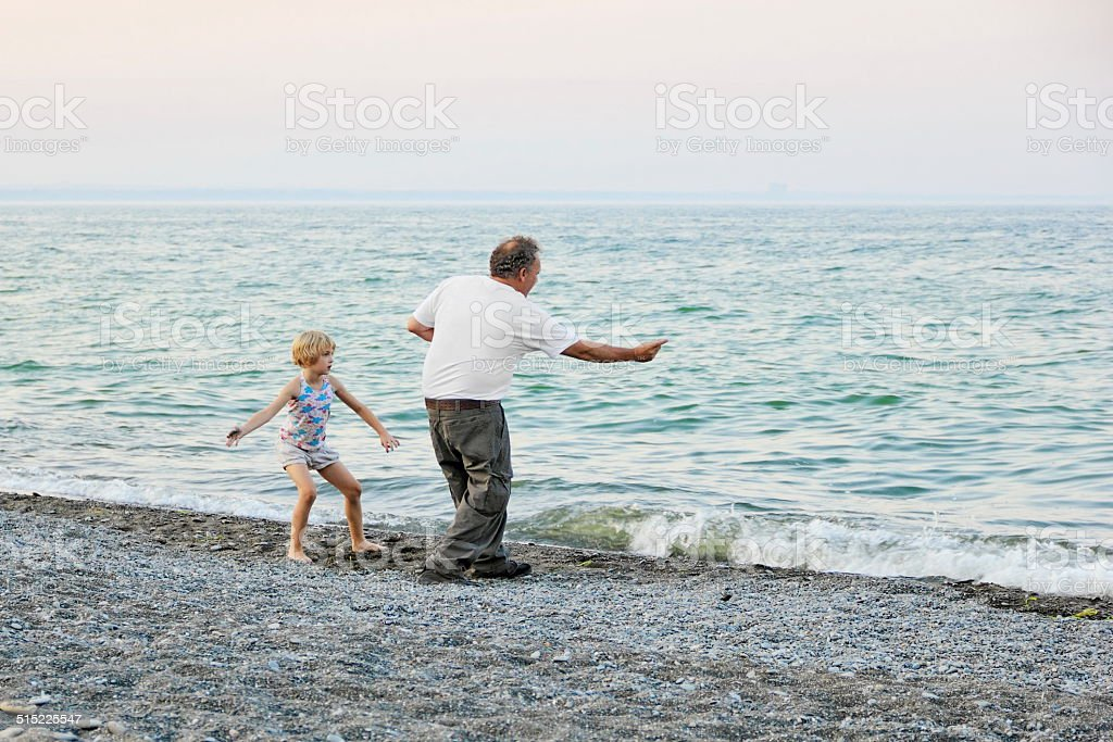 Grampa and Granddaughter skipping rocks stock photo