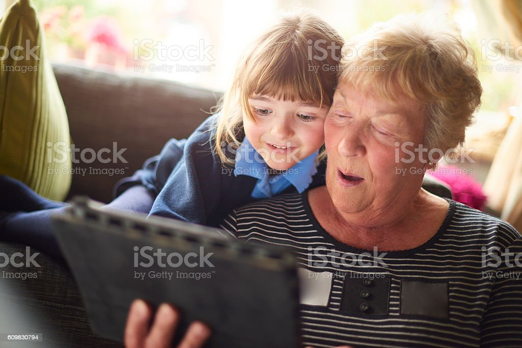 gran and granddaughter looking at a digital tablet . stock photo