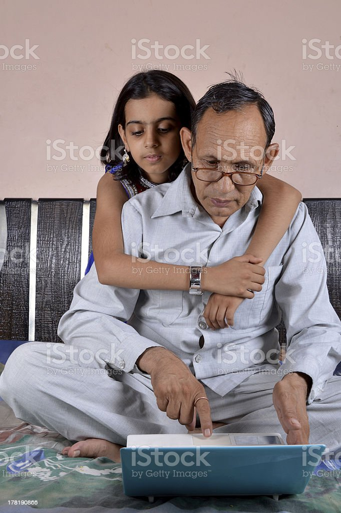 Grand Father with His Little Daughter Using Laptop royalty-free stock photo