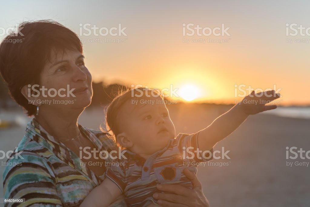 Grand Mother Holding Baby Boy at Beach Sunset stock photo