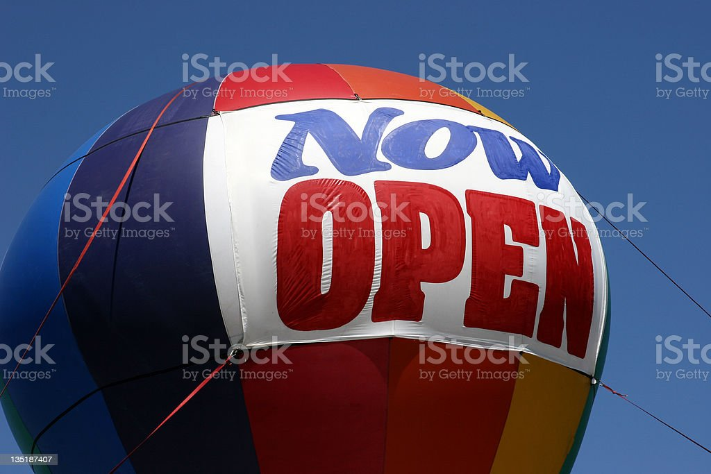 Grand Opening balloon on building top that read Now Open stock photo