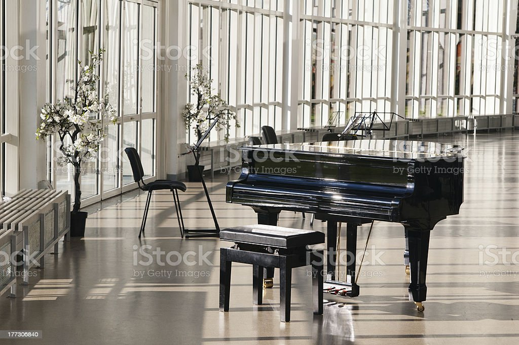Grand piano in the hall shined by sun stock photo