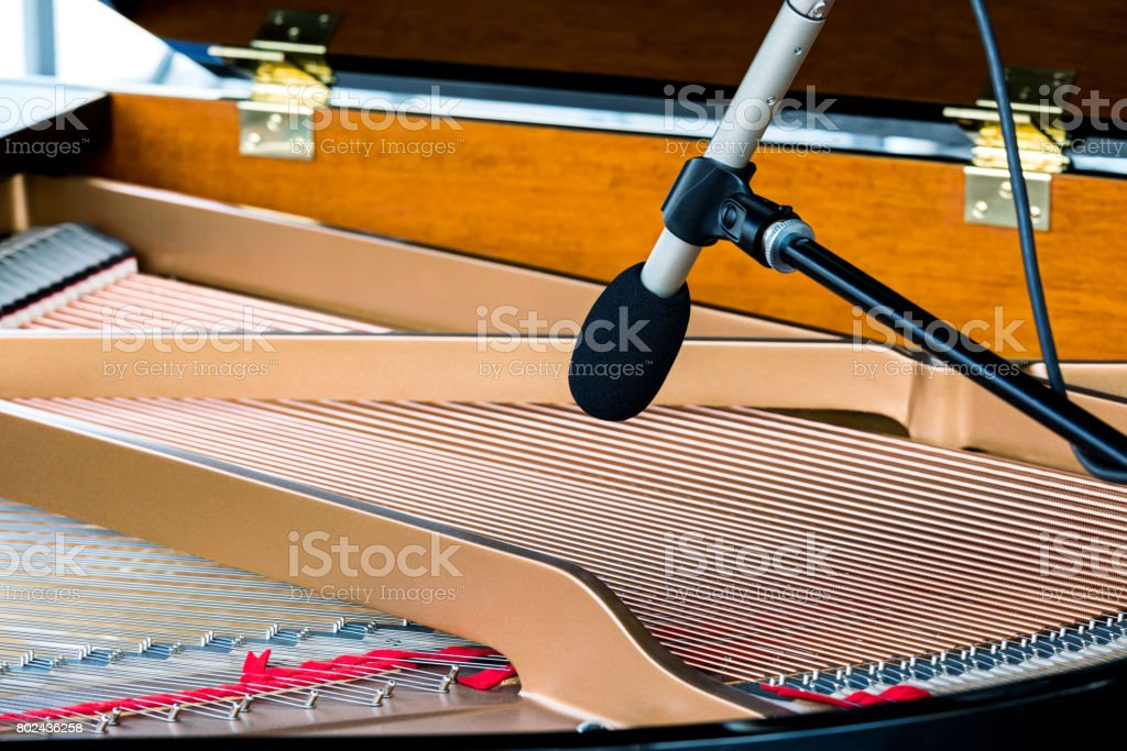 grand piano strings with microphone. musical instruments closeup. stock photo