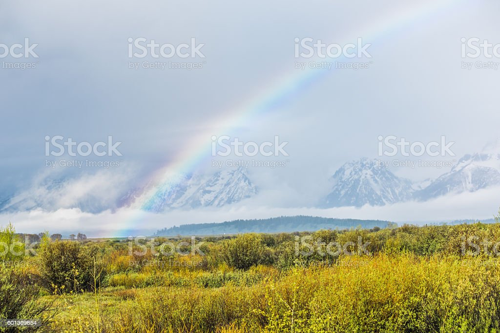 Grand Teton mountains covered with fog and Rainbow stock photo