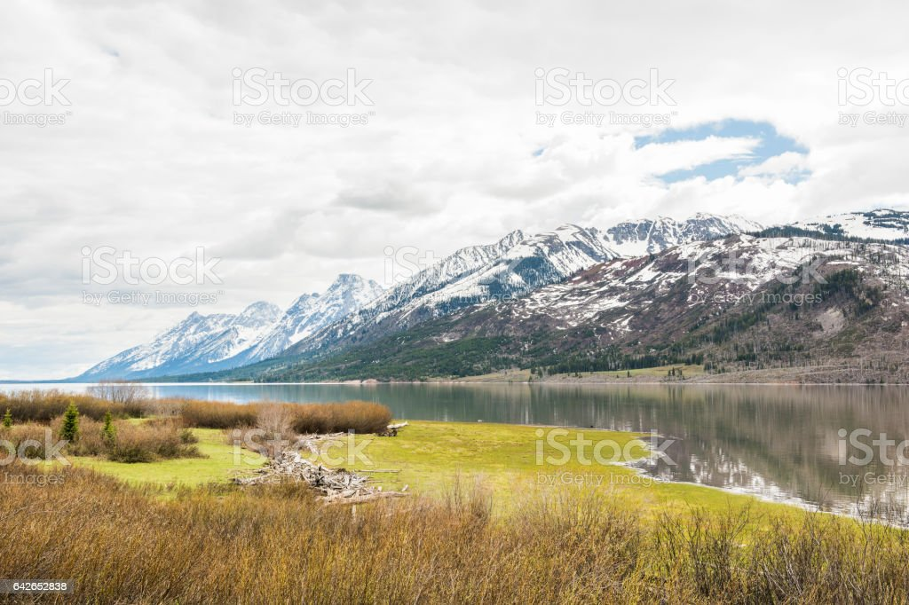 Grand Teton mountains with lake and dark, cloudy, overcast sky stock photo