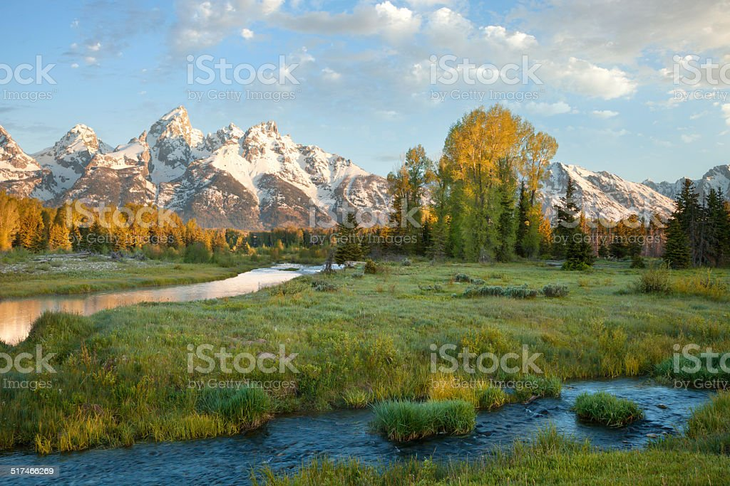Grand Teton mountains with stream in morning light stock photo