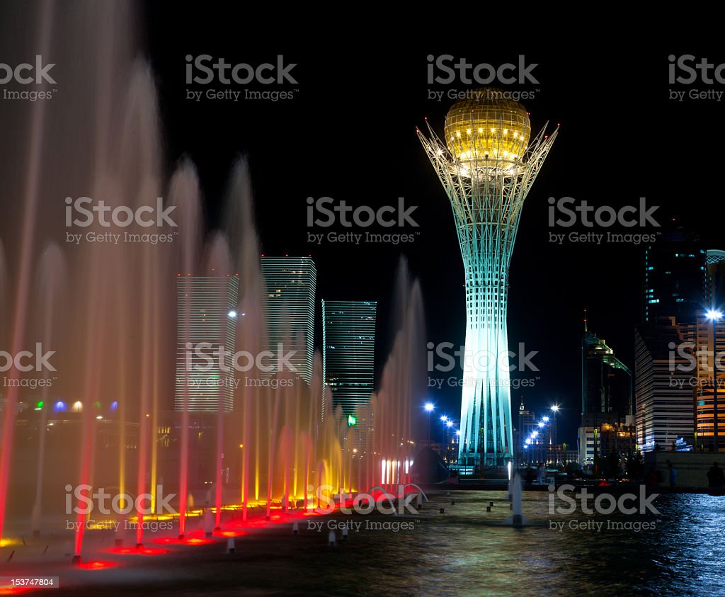 Grand Under lit fountain in front of a ornate tower at night stock photo