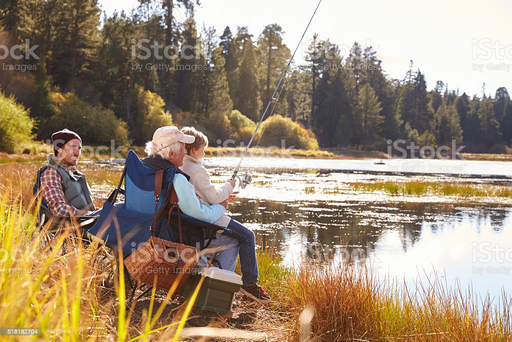 Grandad teaches his grandson to fish at a lake, dad stock photo