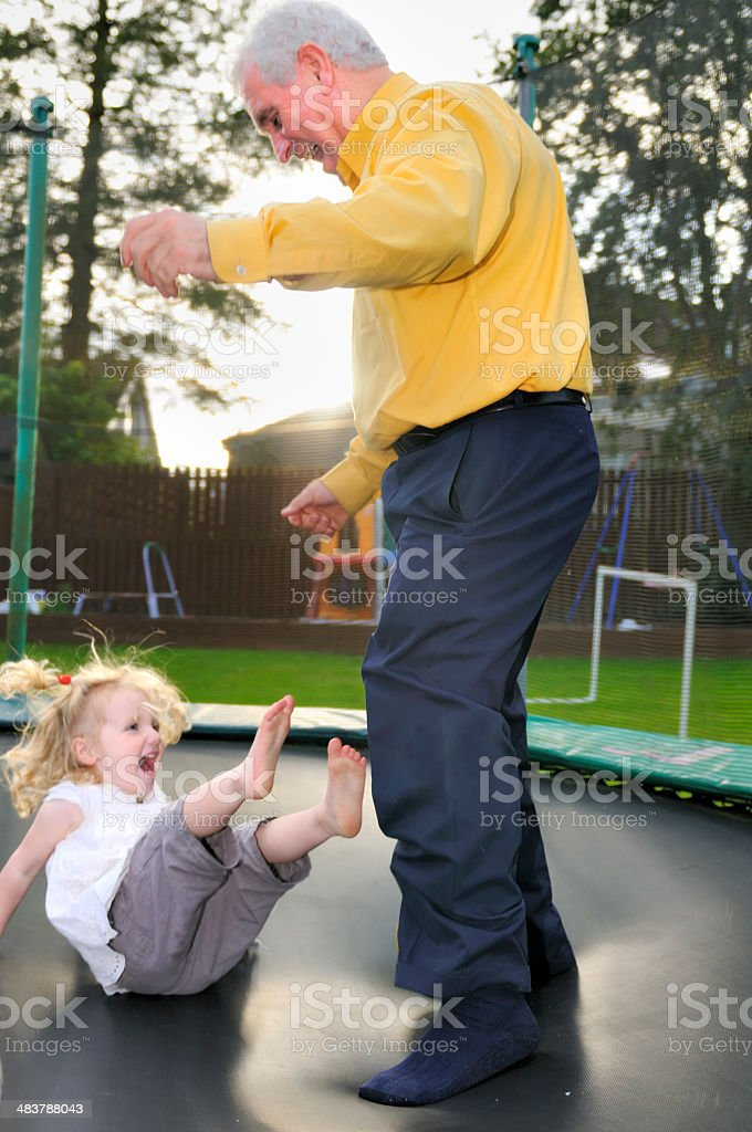 grandaughter and grandfather on trampoline royalty-free stock photo