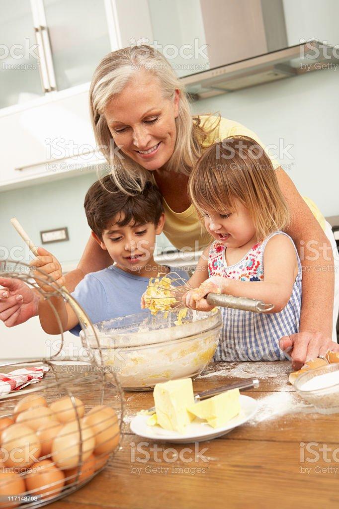 Grandchildren Helping Grandmother To Bake Cakes royalty-free stock photo