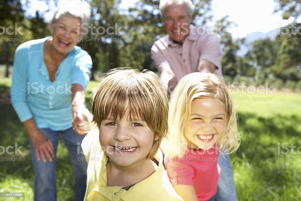 Grandchildren inviting their grandparents to country walk stock photo