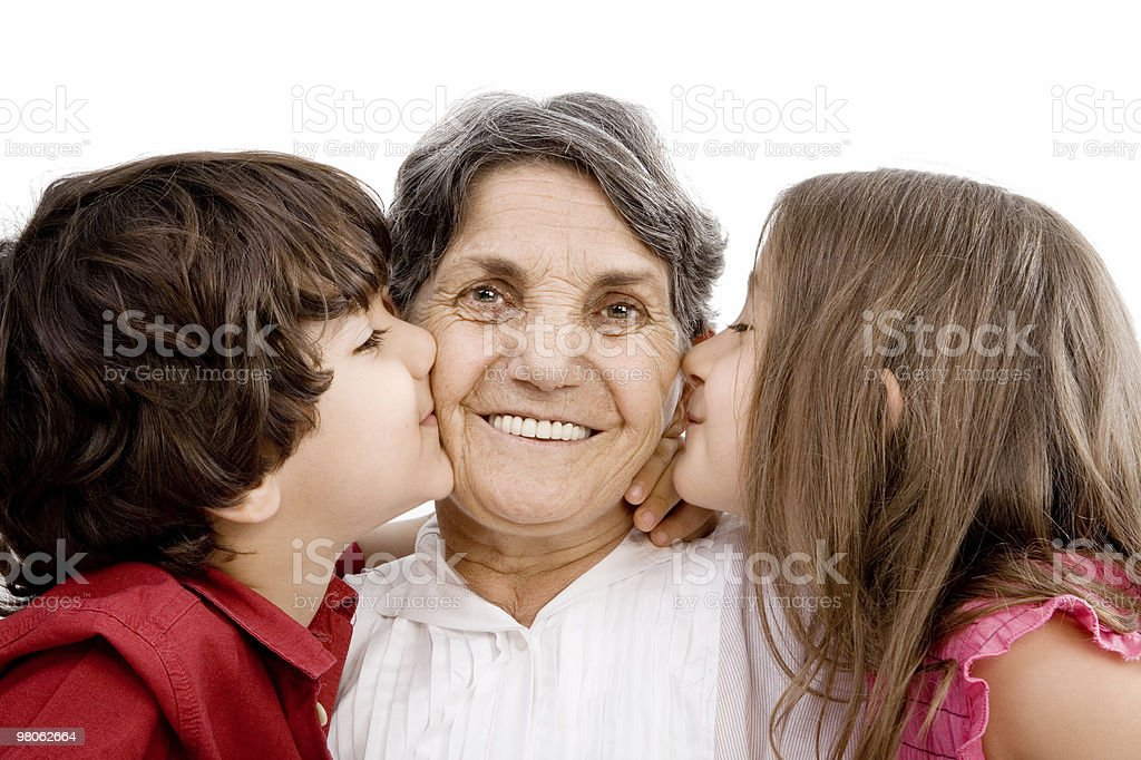 Grandchildren kissing grandmother royalty-free stock photo