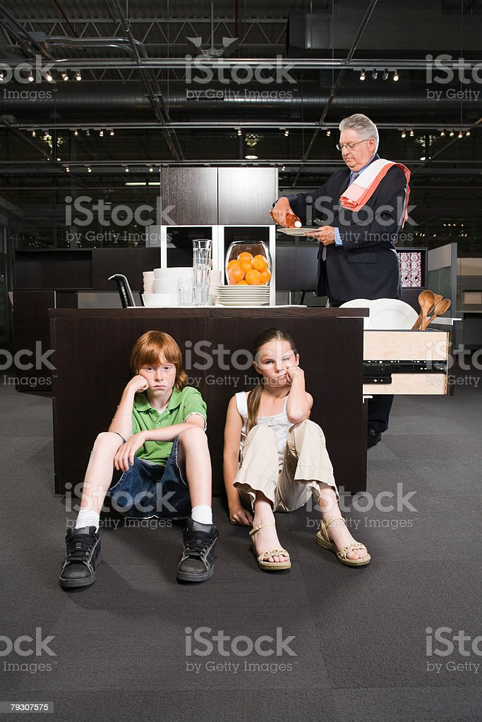 A granddad and grandchildren in a kitchen in an office stock photo