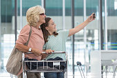 Granddaughter and grandmother taking selfie before boarding.