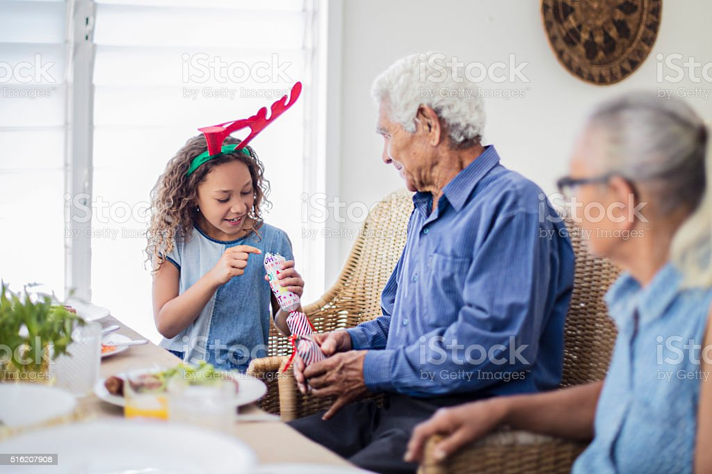 Granddaughter checking Christmas cracker at table after pulling it stock photo