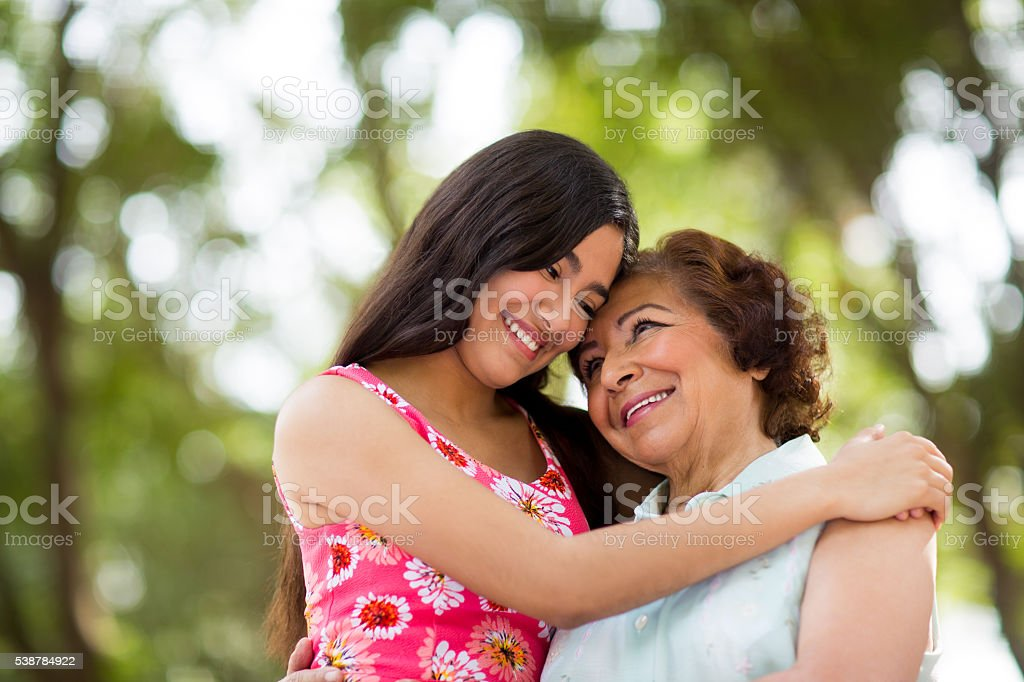 Granddaughter embracing her grandmother stock photo