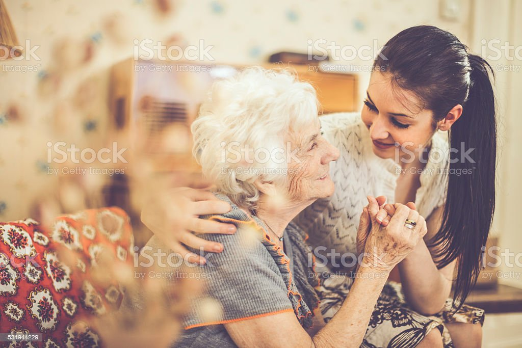 Granddaughter embracing her happy grandmother at home stock photo