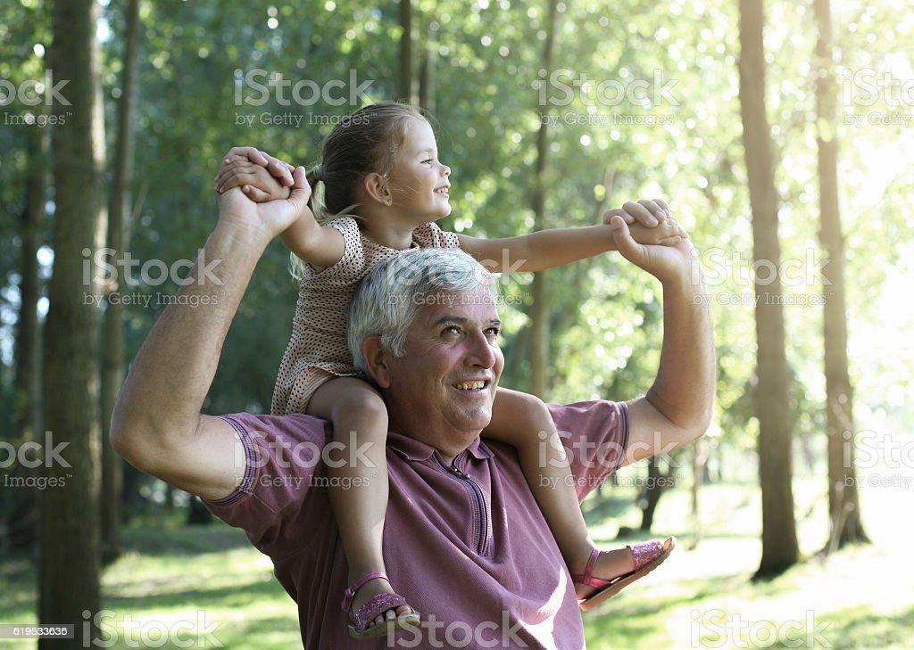Granddaughter enjoying piggyback ride. stock photo