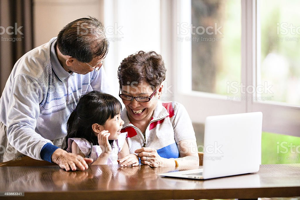 Granddaughter, grandfather and grandmother using laptop stock photo