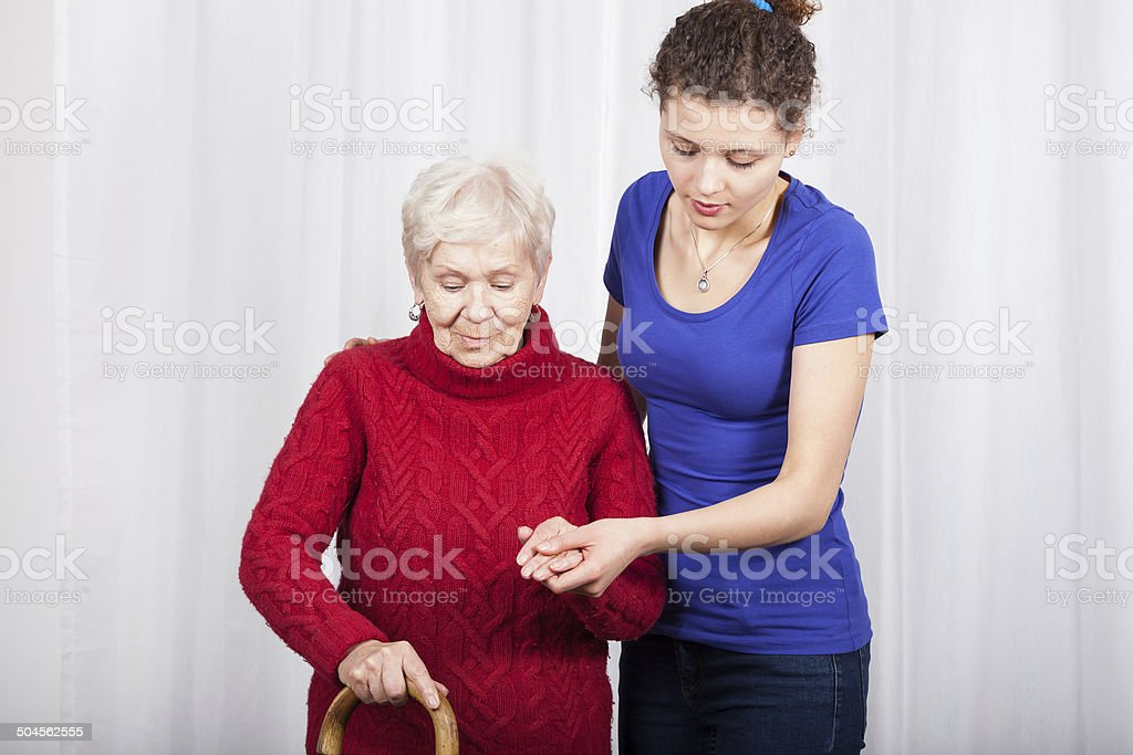 Granddaughter helping grandmother stock photo