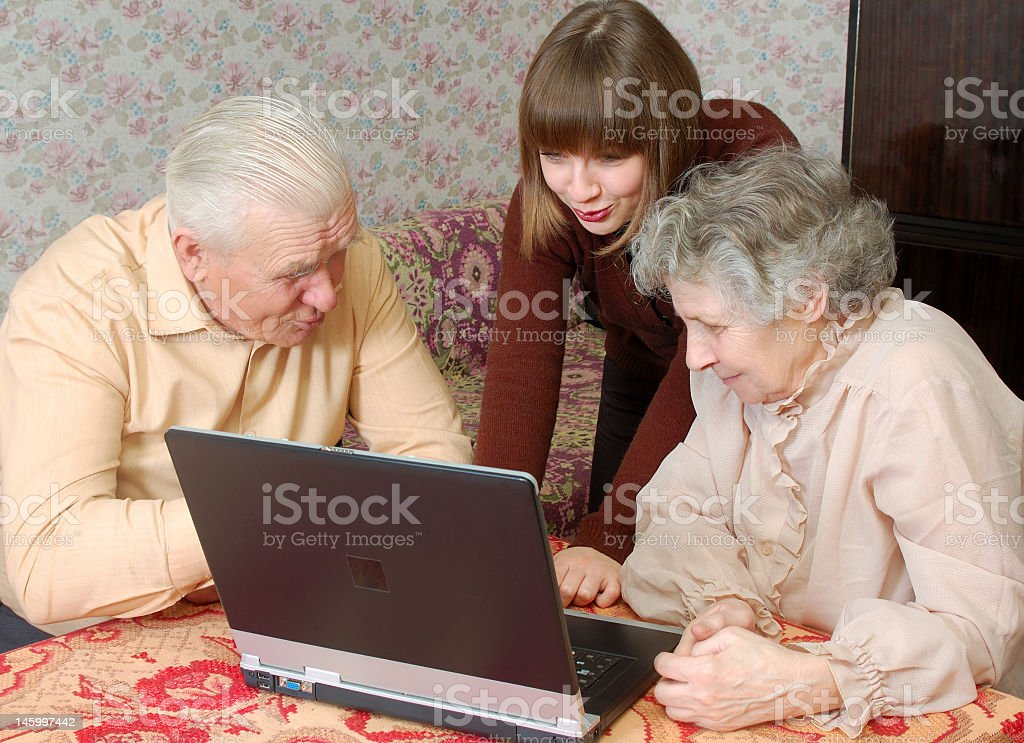 Granddaughter helping grandparents with laptop at the table royalty-free stock photo