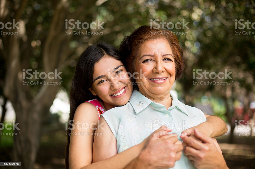 Granddaughter holding her grandmother tight stock photo