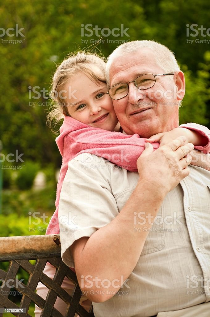 Granddaughter hugging her grandfather from behind royalty-free stock photo