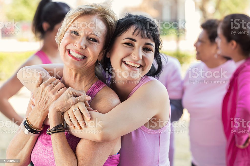 Granddaughter hugs grandmother at charity fun run stock photo