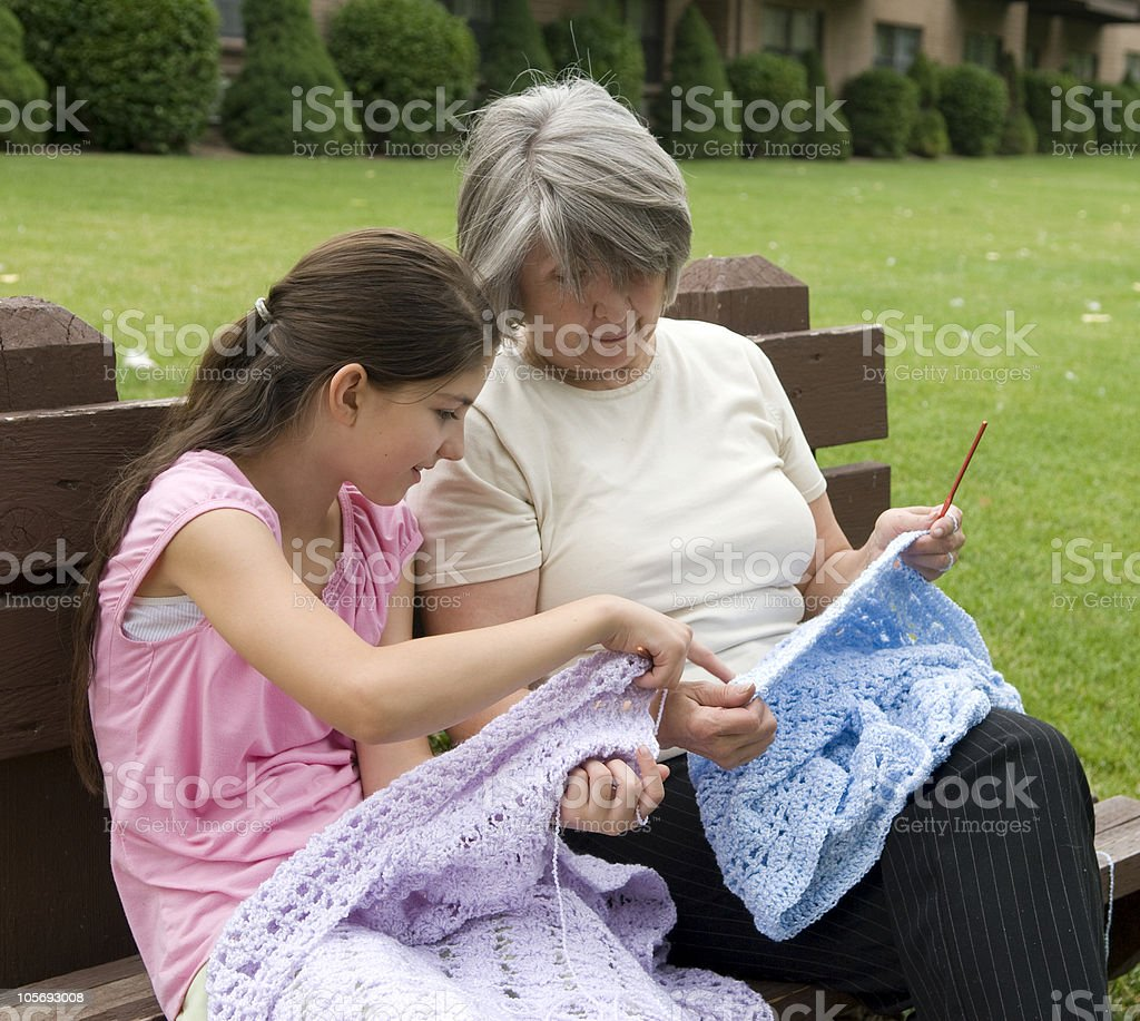 Granddaughter Learning How To Crochet from her Grandmother royalty-free stock photo