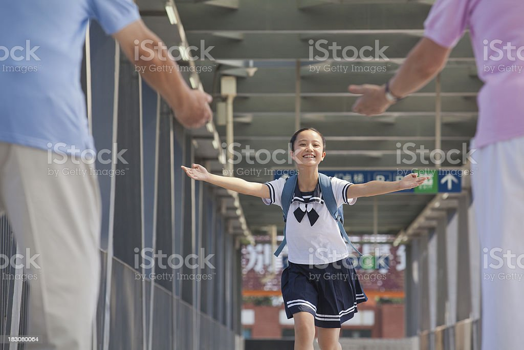 Granddaughter running towards her grandparents royalty-free stock photo
