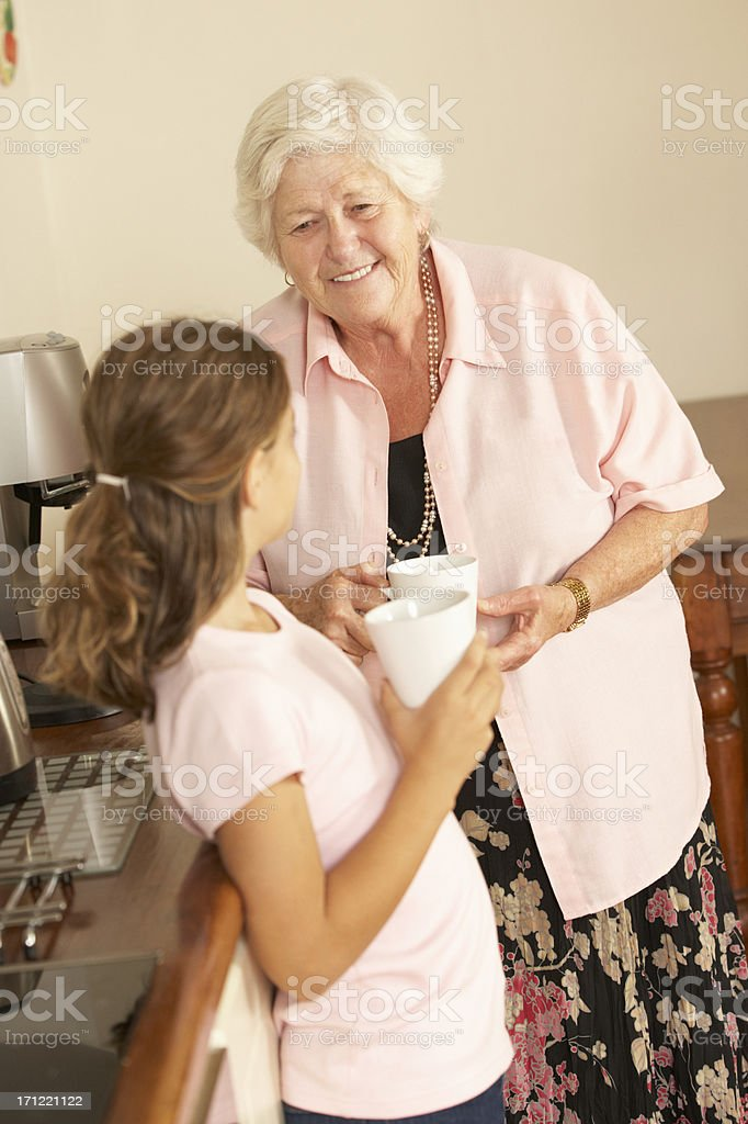 Granddaughter Sharing Cup Of Tea With Grandmother In Kitchen royalty-free stock photo