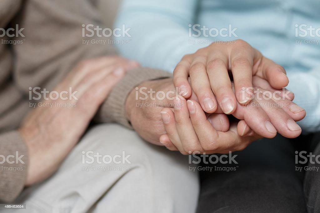 Granddaughter supporting her senior grandpa stock photo