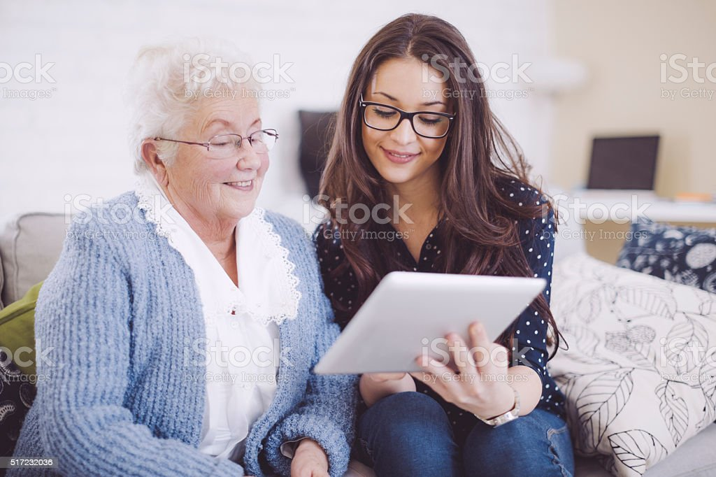 Granddaughter together with her happy grandmother at home stock photo