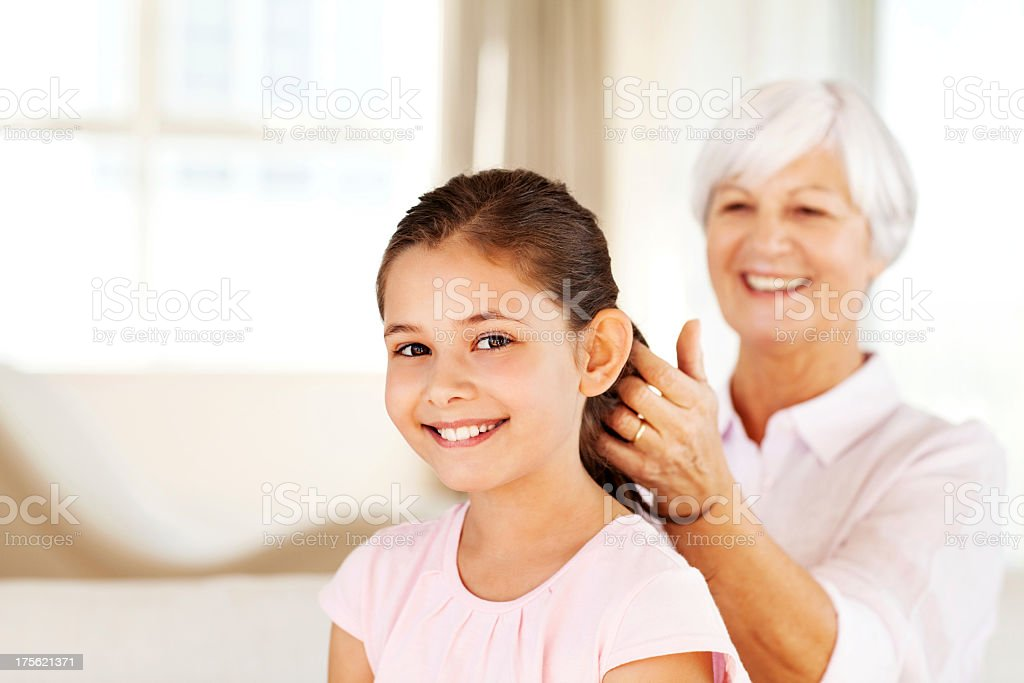 Granddaughter With Grandmother Braiding Her Hair At Home royalty-free stock photo