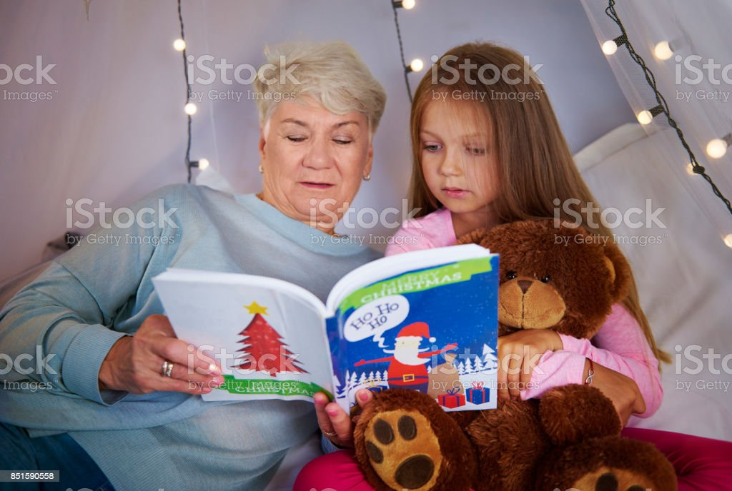 Granddaughter with grandmother watching a picture book stock photo