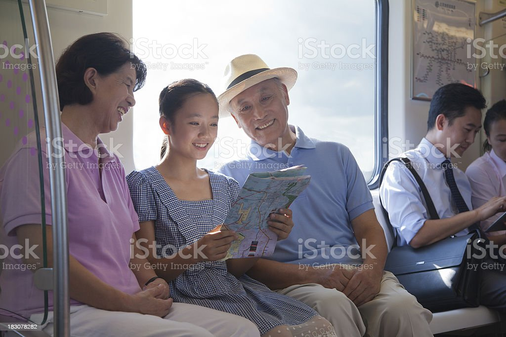 Granddaughter with grandparents looking at the map royalty-free stock photo