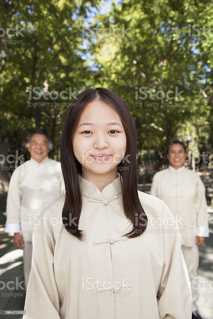 Granddaughter with grandparents practicing Tai Chi royalty-free stock photo