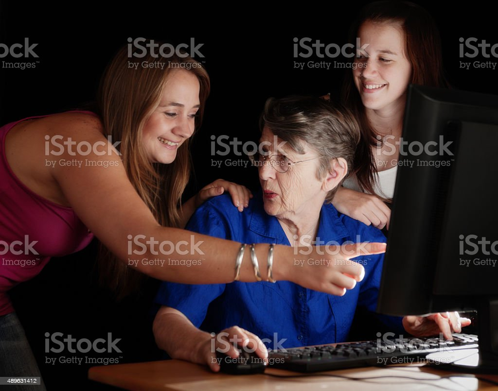 Granddaughters try to teach Granny computer skills but fail stock photo