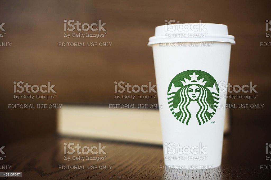 Grande Starbucks to go cup on wooden table with book stock photo