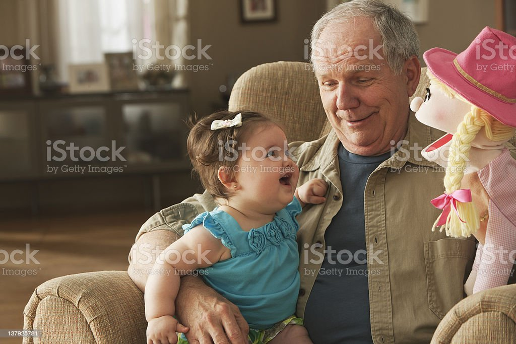 Grandfather and baby granddaughter playing with puppets royalty-free stock photo