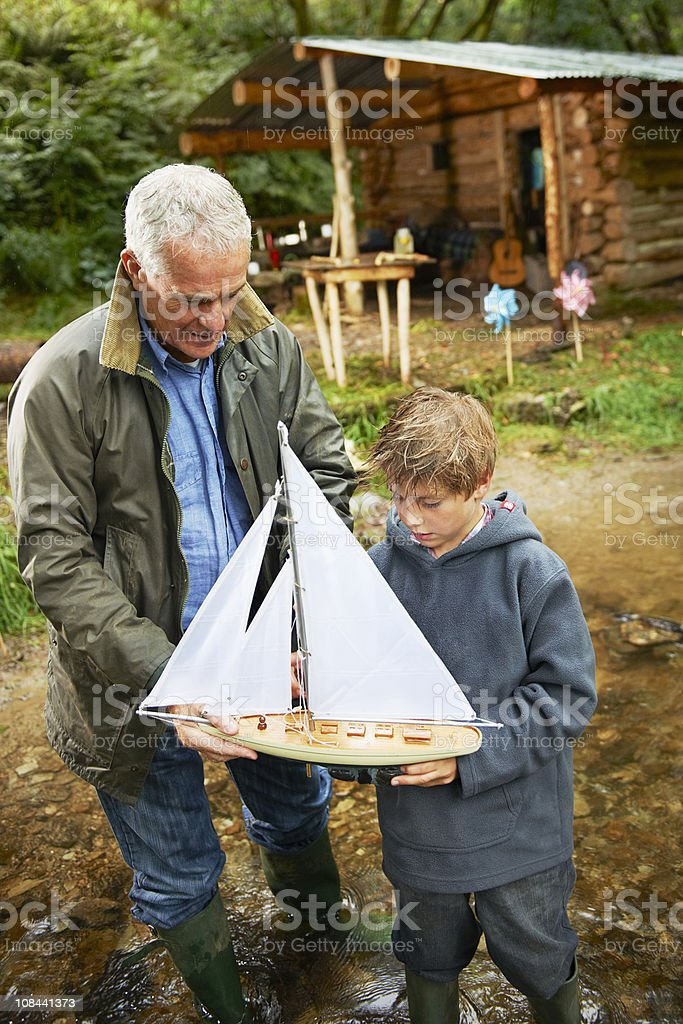 Grandfather and boy with sailing boat stock photo