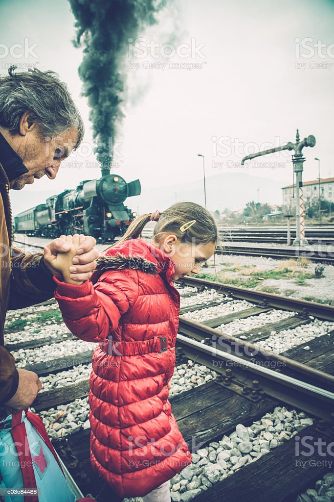 Grandfather and Girl in Pink Admiring Old Steam Train, Europe stock photo