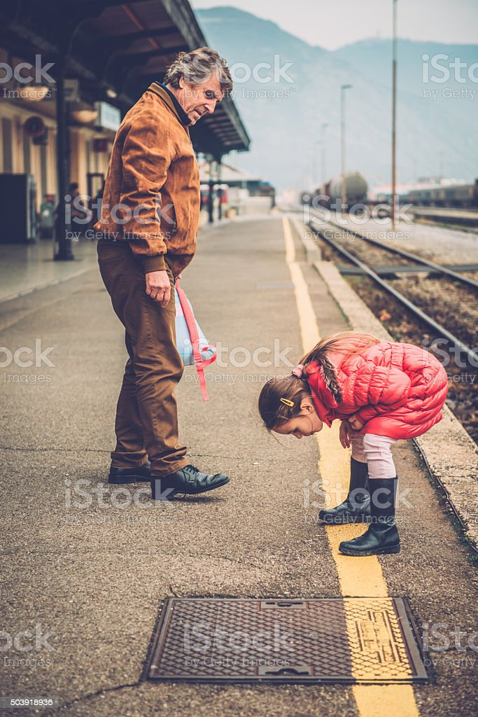 Grandfather and Girl in Pink Enjoying the Railway Station, Europe stock photo