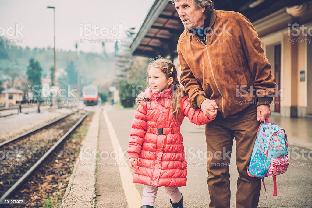 Grandfather and Girl in Pink Walking on Railway Station, Europe stock photo