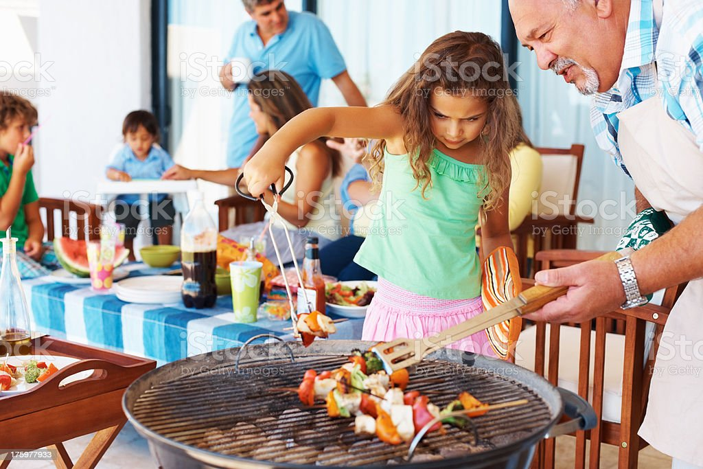 Grandfather and grand daughter barbecuing with family in the background stock photo