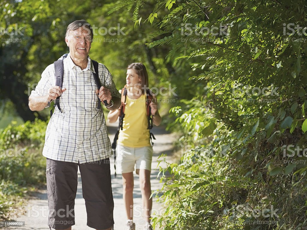 grandfather and grandaughter hiking in wood royalty-free stock photo