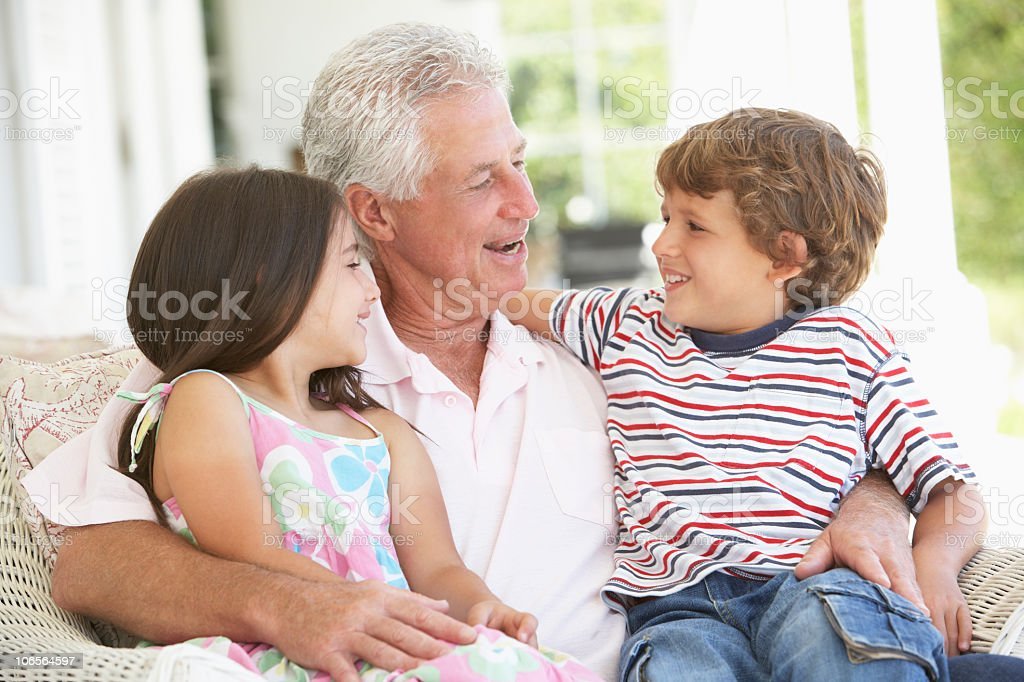 Grandfather And Grandchildren Relaxing In Chair royalty-free stock photo